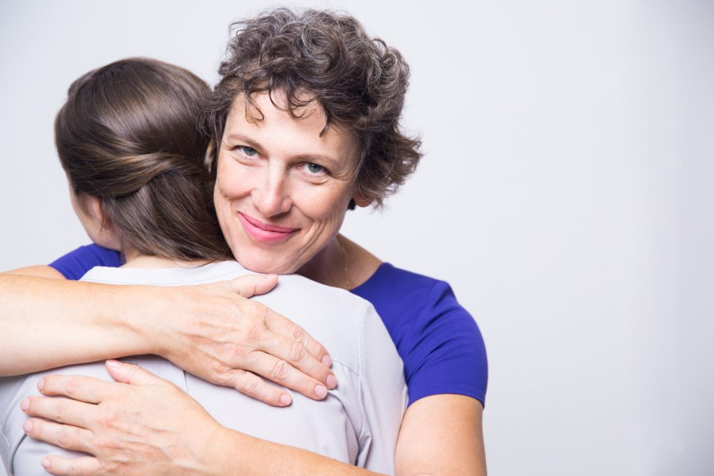 Studio portrait of happy senior woman embracing young adult daughter, looking at camera and smiling