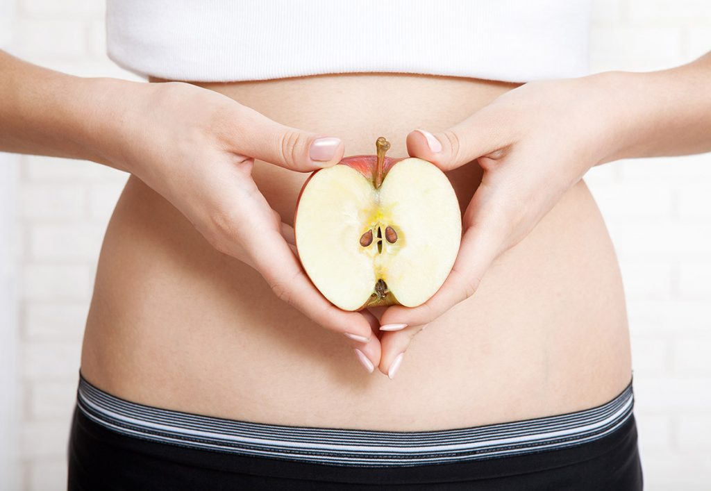 Pregnancy or diet concept, female hands holding apple.